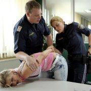 Doris Hindinger wird von 2 Polizisten auf den Tisch gedrückt
